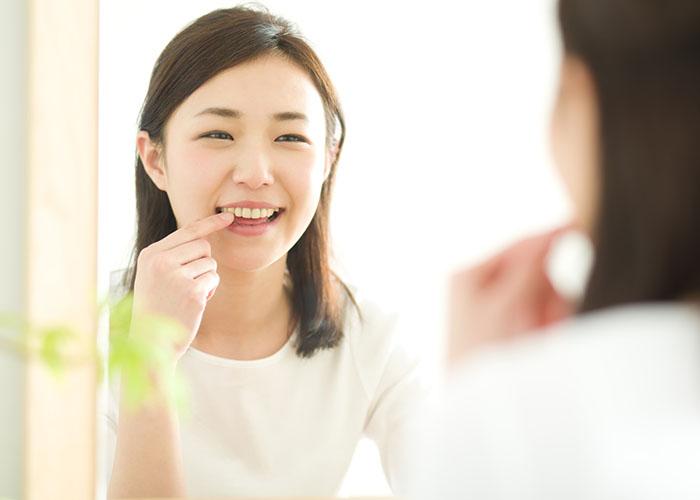 鏡で歯を確認する女性